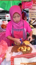 Cutting up cucur udang (battered prawn fritters)